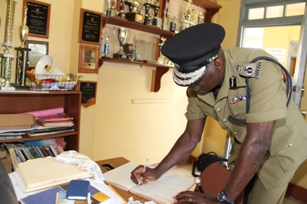 Commissioner of Police in the Royal St. Christopher and Nevis Police Force Celvin G. Walwyn signing the Visitor's Book at the Gingerland Secondary School