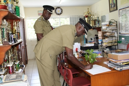Commissioner of Police in the Royal St. Christopher and Nevis Police Force Celvin G. Walwyn signing the Visitor's Book at the Joycelyn Liburd Primary School with ACP Robert Liburd