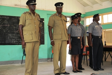 Commissioner of Police in the Royal St. Christopher and Nevis Police Force Celvin G. Walwyn, Assistant Commissioner of Police responsible for the St. Christopher and Nevis Royal Police Force Nevis Division Robert Liburd, Sergeant in charge of the Gingerland Police Station Paulette Bartlette and other officers stationed at the Gingerland Police Station standing at attention during a rendition of the national anthem at the Gingerland Secondary School