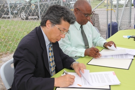 Japanese Ambassador Mr. Yoshimasa Tezuka (r) sings the Grant Agreement and Exchange of Notes with Premier of Nevis Hon. Joseph Parry (l) at Gallows Bay in Charlestown on April 27, 2012