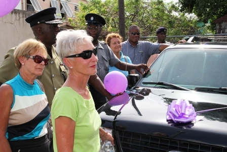 (Front to back) Vehicle donor's wife Mrs Higginbotham, her friend, Commissioner of Police in St. Kitts and Nevis Mr. Celvin G. Walwyn, Four Seasons Resort Director of Residences Ms. Karen Davella and Four Seasons Resort Director of Safety and Lost Mr. Zenric Hanley with officers stationed in Nevis during the blessing of the vehicles