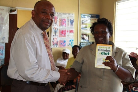 Minister of Health on Nevis Hon. Hensley Daniel presents a health guide on diabetes to Nurse in Charge at the Combermere Health Centre Mrs. Janice Williams