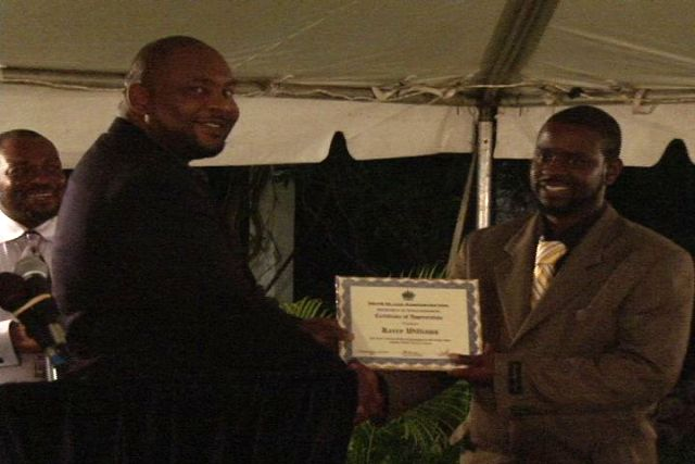 (L-R) Director of the Department of Information Mr. Huey Sargeant presents award to Mr. Kerry Williams at the Department of Human Resource's Award Ceremony for Young Civil Servants, held at the Botanic Gardens. Permanent Secretary Mr. Chesley Manners looks on