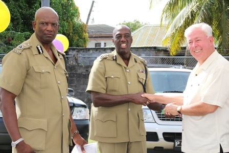 Commissioner of the Royal St. Christopher and Nevis Police Force Celvin G. Walwyn (middle) receives keys to the vehicles from Four Seasons Resort Home Owner Mr. Higginbotham (right). Assistant Commissioner of Police in charge of the Nevis Police Division Mr. Robert Liburd (left) looks on