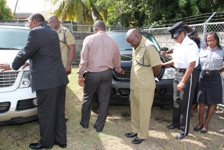 Force Chaplin Pastor Leroy Benjamin (l) blessing the vehicles donated to the Nevis Police Division while officers stationed there join in prayer