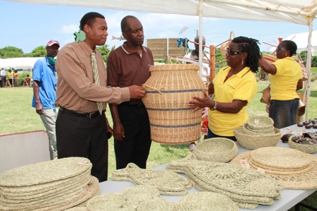 (L-R) Junior Minister of Trade and Industry on Nevis Hon. Dwight Cozier, standing beneath a handmade wooden underwater themed wind chime takes a close look at a hand woven basket with Permanent Secretary in the Ministry of Trade Mr. Dwight Morton and General Manager of the Nevis Craft House Ms. Doretta Daniel. They are standing next to a variety of straw items on display