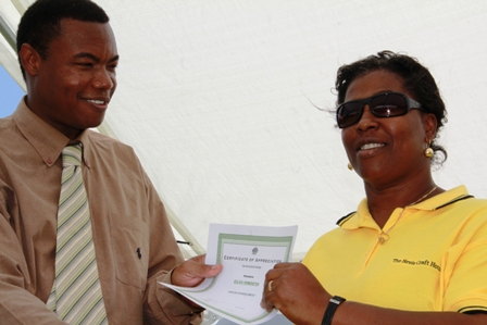 Minister of Trade awards the longest serving worker at the Nevis Craft House Ms.  Eulica Pemberton for 32 years of service