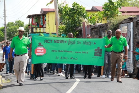 Premier of Nevis and Minister of Education Hon. Joseph Parry (left) and Deputy Premier and Minister responsible for Social Development Hon. Hensley Daniel (right) carry the banner and lead the Child Month Parade 2012 through Charlestown along with (L-R second row) (partly hidden) Permanent Secretary in the Ministry of Education Mrs. Lornette Queeley-Connor, Cabinet Secretary Mr. Ashley Farrell, Advisor to Health Mrs. Patsy Hanley and Minister of Agriculture and Area Representative Hon. Robelto Hector