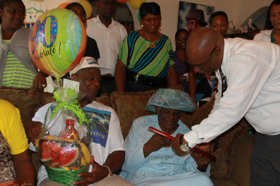 Premier of Nevis, Hon. Joseph Parry giving gifts to Mrs. Rosalie Martin on her 90th Birthday