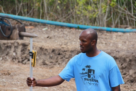 Works Engineer Mr. Dillon Webbe shooting levels with a laser level for the excavator during preparatory works for a new 500,000gallon reservoir at the Spring Hill site under the Nevis Water Enhancement Project funded by the Caribbean Development Bank