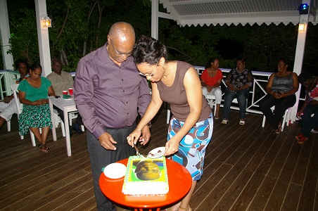 Premier of Nevis, Hon. Joseph Parry cutting his cake with the assistance of his daughter Sonya Parry
