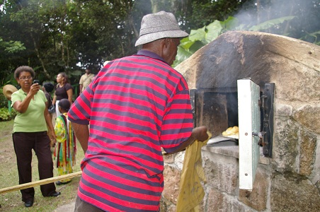 Mr. Herbert taking out the freshly made bread from the old fashion stove oven