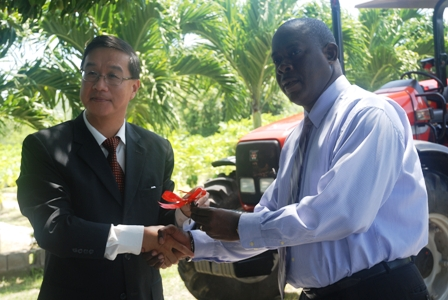 (L-R) Ambassador of the Republic of China/Taiwan to St. Kitts and Nevis His Excellency Miguel Tsao handing over the keys to a new Massey Ferguson tractor to Minister of Agriculture on Nevis Hon. Robelto Hector at the Taiwanese Mission at Cades Bay