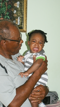 NevCan Cultural Association's Vice President Mr. Hugh Jeffers visits with baby K'yun Elliott at his home in Stoneygrove shortly after his grandmother Ms. Rodney Elliott was presented with financial assistance to help defray cost of medical expenses when he was newly born
