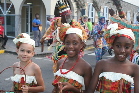 Three young Nevisian ladies with masqueraders in the background taking part in the official cultural parade to launch Culturama 2008 (file photo)