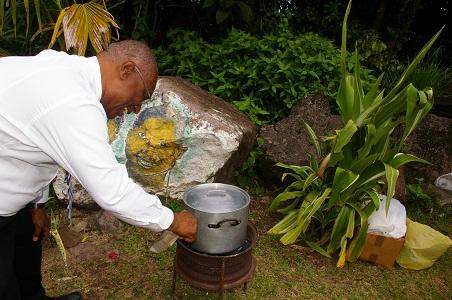 Premier Parry fanning the coal pot with Cassava mussa