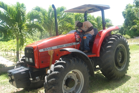 A member of staff of the Department of Agriculture on Nevis trying out the US$38,500 Massey Ferguson tractor, a gift from the Government of the Republic of China/Taiwan for use by the Department in its land preparation programme