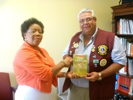 District Governor Zone 60B Mr. Claudius 'Tony' Boncamper MJF hands over books to Director of the Nevis Library Services Mrs Sonita Daniel