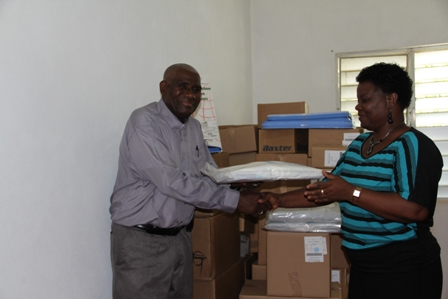 Director of the Development Projects Foundation Mrs. Myrthlyn Parry, hands over a donation of medical supplies from charitable US based organisation Hospital Sisters Mission, to Chairman of the Board of Directors of the St. Georges and St. Johns Senior Citizens Home in Gingerland Reverend Cannon Dr. Alson Percival