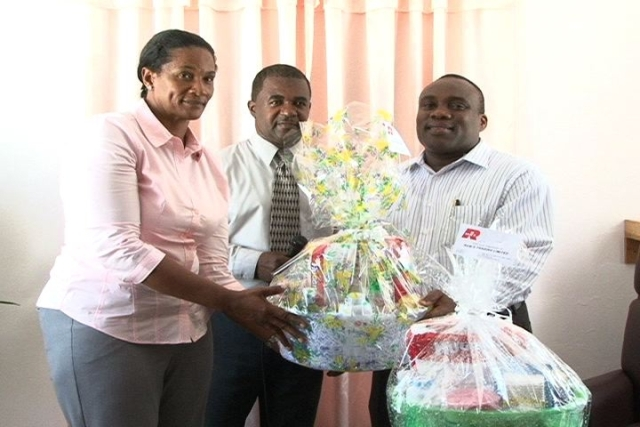 (L-R) Rams Group of Companies Representative Ms. Shirley Julius presents baby hampers to Medical Chief of Staff Dr. John Essien while Acting Hospital Administrator Mr. Johnson Morton and Matron Aldris Pemberton Dias (out of photograph) look on