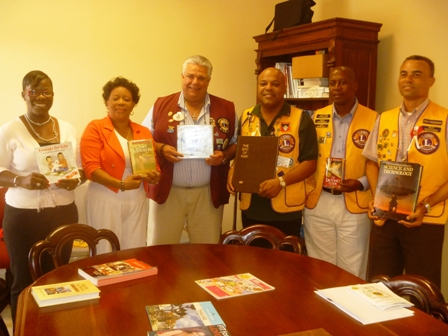 (L-R) Mrs. Marva Roberts from the Nevis Library Services, Director of the Nevis Library Services Mrs Sonita Daniel, District Governor Zone 60B Mr. Claudius 'Tony' Boncamper MJF, Zone Chairman of the Antigua Lions Club Mr. Lester Ephraim, President of the Nevis Lions Club Mr. Cartwright Farrell and Immediate Past president of the Nevis Lions Club Mr. Ernie France show off books donated by the Lions Club