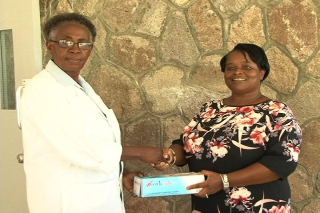 (L-R) Nurse Manager at the Flamboyant Nursing Home Ms. Ena Sutton receives donation from Nevisian Ms. Earlene Byron and other members of her family all based in the United Kingdom.
