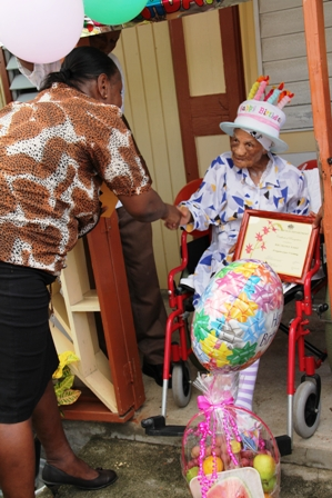 Director of Social Services Ms. Sandra Maynard making presentations to birthday girl Mrs. Selina Ward during her 101 birthday celebrations