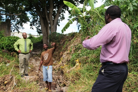 Project Manager for Contractors Surrey Paving &Aggregate Co. Caribbean Ltd. Mr. Desmond Lewis (right) with Lower Stoney Grove resident Mr. Dale Claxton (middle) and Premier of Nevis Hon. Joseph Parry during a walkthrough of the Bath Ghaut to see firsthand the damage caused by flood waters