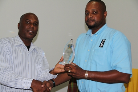Permanent Secretary in the Ministry of Youth and Sports Mr. Alsted Pemberton presents award to Lester Liburd for his contribution to Culture