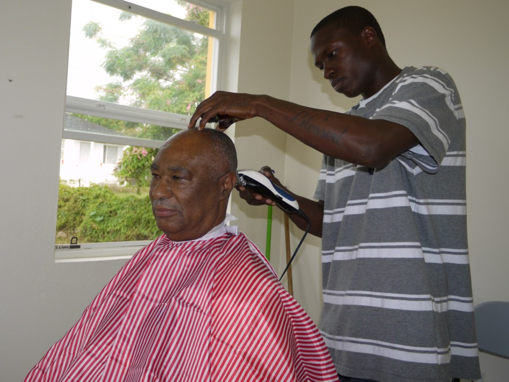Nevis Premier Honourable Joseph Parry receives a haircut from Mr. Analdo Browne of Fresh Look Beauty Salon and Barber'n