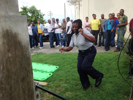 Fire Sub Officer based at the Charlestown Fire Station on Nevis Ms. Catherine Joseph takes part in a simulation exercise while other participants at the Community Emergency Response Team (CERT) training workshop look on