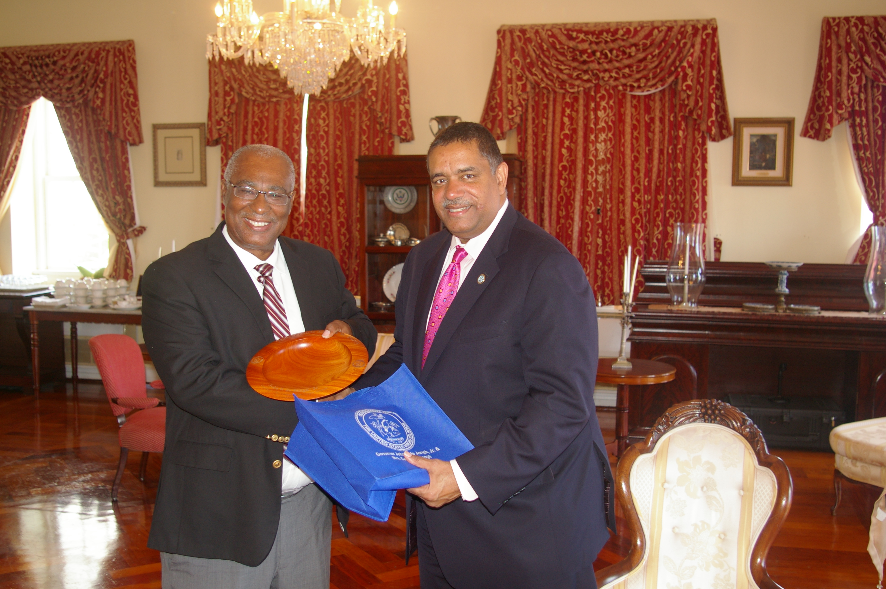 Premier, Hon. Joseph Parry receiving a gift of a local woodcarving from the Governor of the United States Virgin Islands (USVI), the Hon. John P. de Jongh