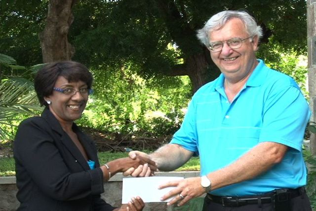 "President of the Tarsus Trust Co. Ltd. Mr. Thomas ""Tom"" Ferneau hands over a cheque of over $US12, 000 on behalf of his Company and associates Alan and Jayneen Ross of Oklahoma, to the Society's Treasurer Ms. Paulette Hanley"