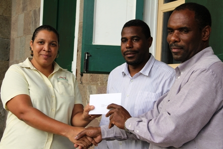 Support Coordinator Pink Lilly Cancer Care Group Ms. Tracy Parris (l) receiving a donation from President of the St. Georges Development and Enhancement Committee Mr. Collin Dore (r) and group member Mr. Devon Liburd (middle) on behalf of their group and the community for fellow villager Ms. Rubylette Chapman