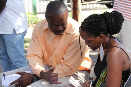 Consultant with the Sugar Industry Diversification Fund (SIDF) and Coordinator for the Small Entrepreneur and Enterprise Development (SEED) initiative funded by the SIDF Mr. Greg Phillip assists an applicant just after the official launch at the Memorial Square in Charlestown, Nevis on December 21, 2012