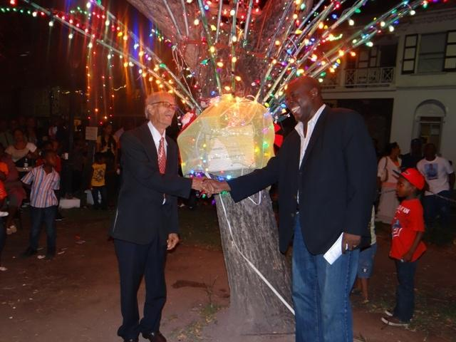 A joyous moment for Patron of the 2012 Charlestown Christmas Tree Lighting Ceremony at the Memorial Square in Charlestown Mr. Arthur Evelyn and Area Representative for the St. Pauls Parish and Minister in the Nevis Island Administration Hon. Robelto Hector