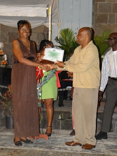 Advisor to the Premier of Nevis Mr. Hensley Daniel presents Certificate of Recognition from the Department of Community Development to honouree in the St. Pauls Parish Ms. Bridgette Hunkins