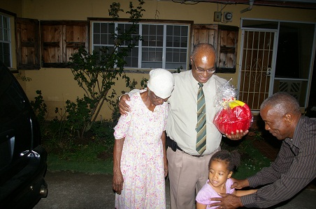Premier of Nevis, Hon. Joseph Parry and Cabinet Secretary, Mr. Ashley Farrell giving a gift basket to Mrs. Inez Claxton and her granddaughter for her long-time support to him in recognition of his 25 years of service to Parliament