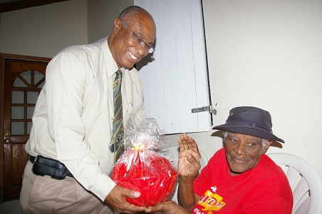 Premier Parry giving a gift basket to Mrs. Rose Martin of Jessups village on his 25th anniversary of elected office