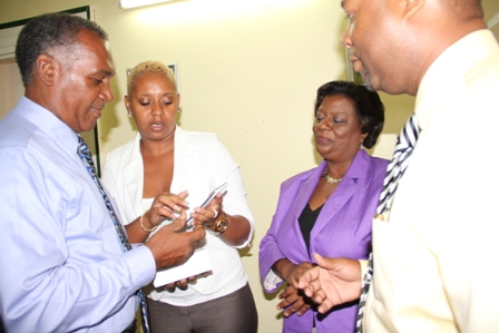 St. Kitts and Nevis Corporate Sales Manager Ms. Jacinth Welsh gives Premier Vance Amory a crash course in the use of the Digicel Galaxy S3 handset donated by her Company while her colleagues Retail Sales and Distribution Manager Ms. Kaye M. Woods and Digicel's Country Manager Mr. Sean Latty look on