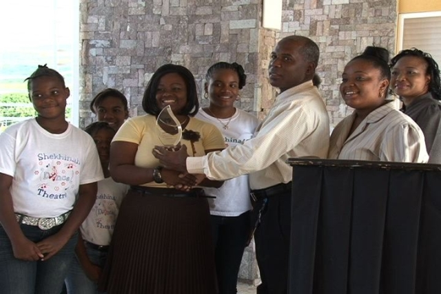 Permanent Secretary in the Ministry of Social Services on Nevis Mr. Alsted Pemberton presents a plaque to President and co founder of the Shekhinah Dance Theatre Mrs. Tamicia Lestrade in the presence of group members. Youth Development Officer in the Ministry of Social Services Ms. Vieda Leiser Mills (second from right) looks on