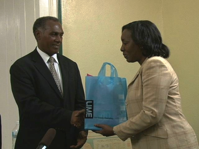 Premier of Nevis Hon. Vance Amory receives a Blackberry handset from LIME's Corporate Accounts Managers Mrs. Eunice George