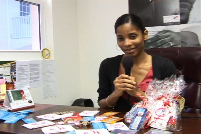 "HIV/AIDS Unit Coordinator, Health Promotions Unit in the Ministry of Health on Nevis Mrs. Nadine Carty-Caines with a sample of the ""love package"" for distribution at the Memorial Square in Charlestown on Valentine's Day"