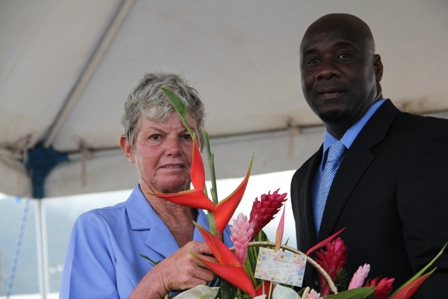 30 year-long Livestock Farmer on Nevis and Patron of the 2013 Agriculture Open Day on Nevis Mrs. Sandra David, is presented with a floral arrangement by Minister of Agriculture Hon. Alexis Jeffers