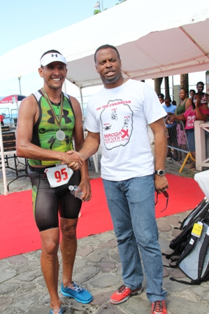 Deputy Premier of Nevis and Minister of Sports Hon. Mark Brantley greets decorated Triathelete Chris McCormack, winner of the first ever MaccaX Nevis International Triathlon held on Nevis on November 16, 2013