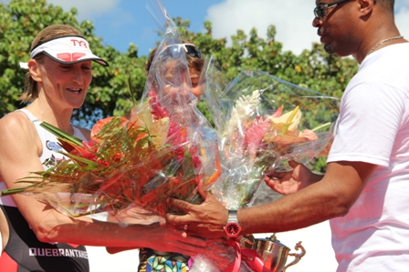 Current Age Group European Champion triathlete Jane Hansom receives flowers handed to her by Deputy Premier of Nevis and Minister of Sports Hon. Mark Brantley for crossing the finish line in third place and the first woman to complete the race in the MaccaX Nevis International Triathlon held in Nevis on November 16, 2013