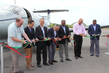 Premier of Nevis Hon. Vance Amory (third from right) cuts the ribbon to signal the official start of Tradewind Aviation's daily service from San Juan to Nevis with Deputy Premier and Minister of Tourism on Nevis Hon. Mark Brantley (extreme right), Federal Minister of International Transport Hon. Richard Skerritt (second from right) along with (l-r) General Manager of the Four Seasons resort, Nevis Mr. Sven Wiedenhaupt and President of Tradewind Aviation Mr. David Zipkin, Vice President of Tradewind Aviation Mr. Eric Zipkin and Mr. David Zara. They are at the tarmac of the Vance Amory International Airport in Newcastle