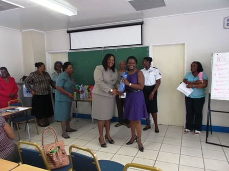 Vice President of the newNevis National Women's Council Mrs. Vernie Amory receives a token from Assistant Secretary in the Ministry of Social Development Ms. Michelle Liburd while other members of the Council look on