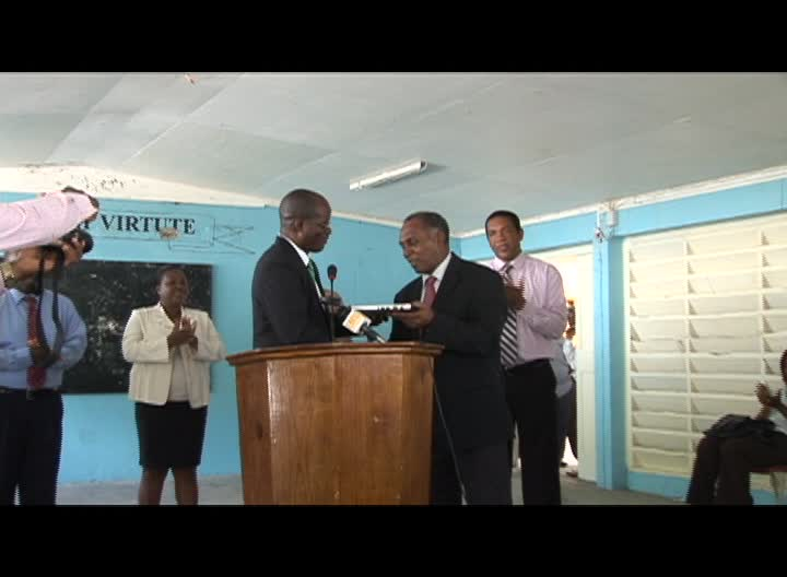 Premier of Nevis and Minister of Education Hon. Vance Amory receives computers from Federal Minister Hon. Patrice Nisbett at the Charlestown Secondary School on November 03, 2013. Looking on (left is Federal Minister Hon. Glen Phillip and Permanent Secretary in the Ministry of Education Mrs. Lornette Queeley-Connor (r)