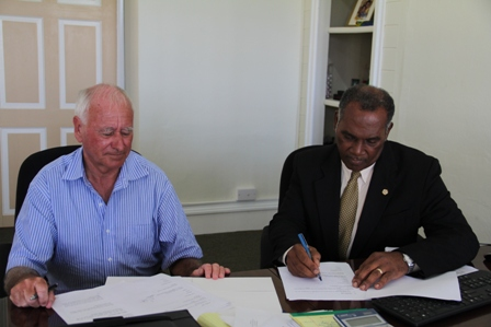 Premier of Nevis Hon. Vance Amory signs documents with Chief Executive Officer of Fly Montserrat Captain Nigel Harris at the Ministry of Tourism's office at Bath Hotel, Bath Plain on December 16, 2013.